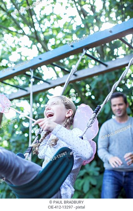 Father pushing daughter on swing outdoors