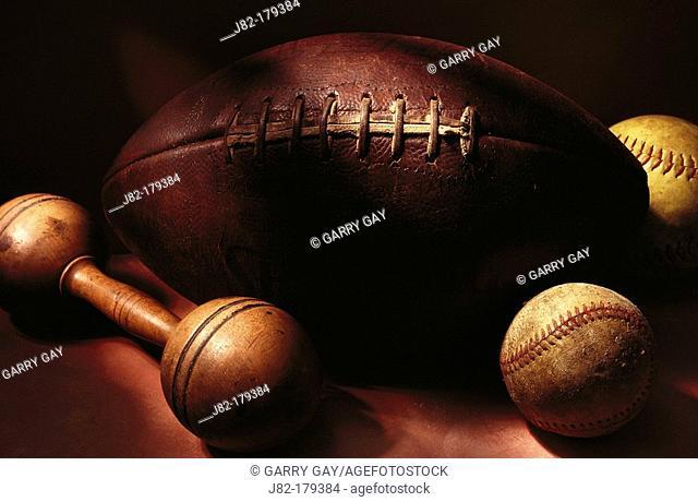 Football, baseball, softball and dumbbell still life