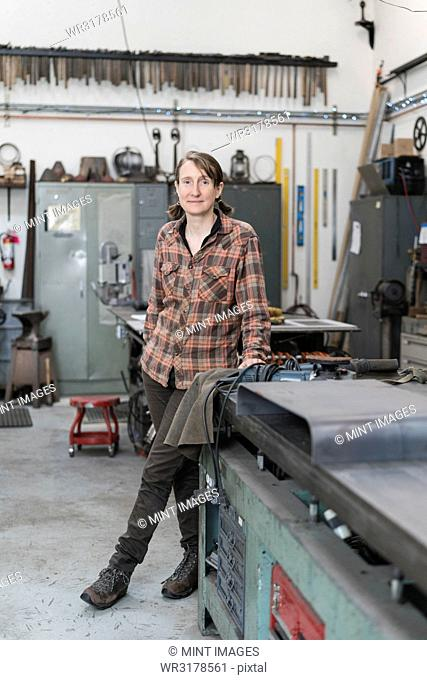 Blond woman wearing checked shirt standing in metal workshop, looking at camera