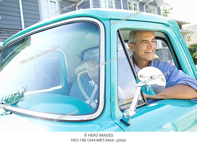 Mature man looking out of window while sitting pick-up truck