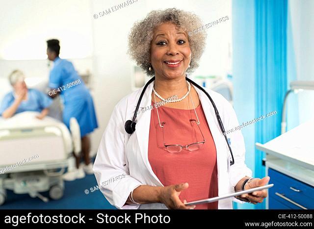 Portrait confident senior female doctor using digital tablet in hospital room