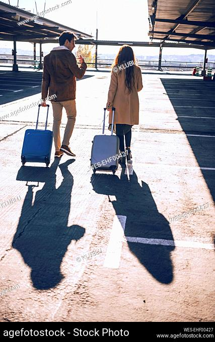 Business couple pulling luggage while walking at airport parking lot during sunny day