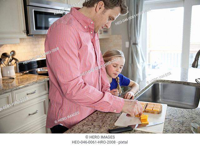 Father preparing sandwich with daughter in domestic kitchen