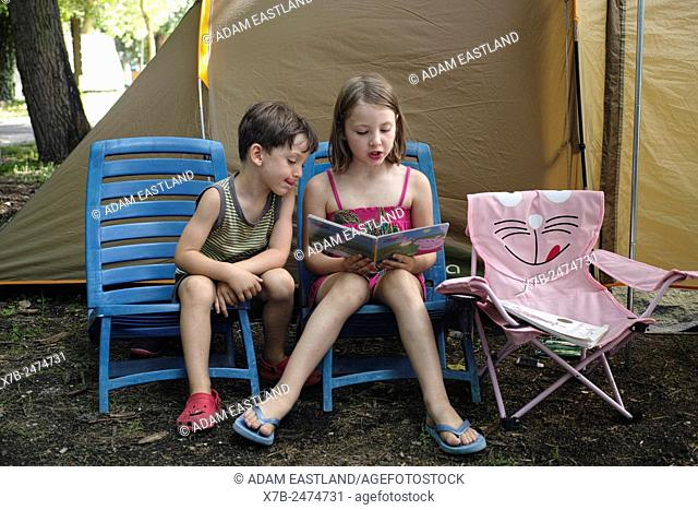 Lago di Bracciano. Lazio. Italy. Six year old girl reading to a younger 4 year old boy on camping holiday