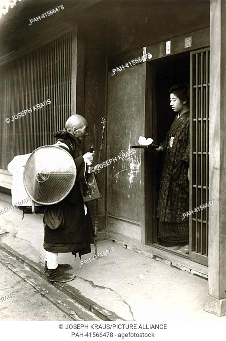 A medicant receives a bowl of tea. Pictured in the early 1920th. - /Japan