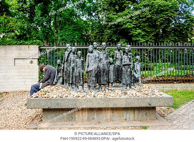 18 July 2019, Berlin: An old man sits at the edge of a group of figures by sculptor Willi Lambert in front of a Jewish cemetery on Grosse Hamburger Straße in...