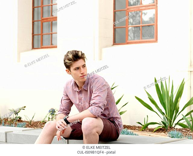 Young man sitting on step, outdoors, looking away