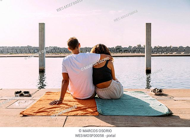 Rear view of young couple sitting on a pier at the sea