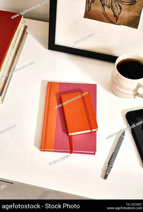 The top of a white glossy desk with a red notebook and pens and coffee and a cell phone