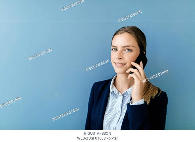 Portrait of a young businesswoman against blue background, talking on her smartphone