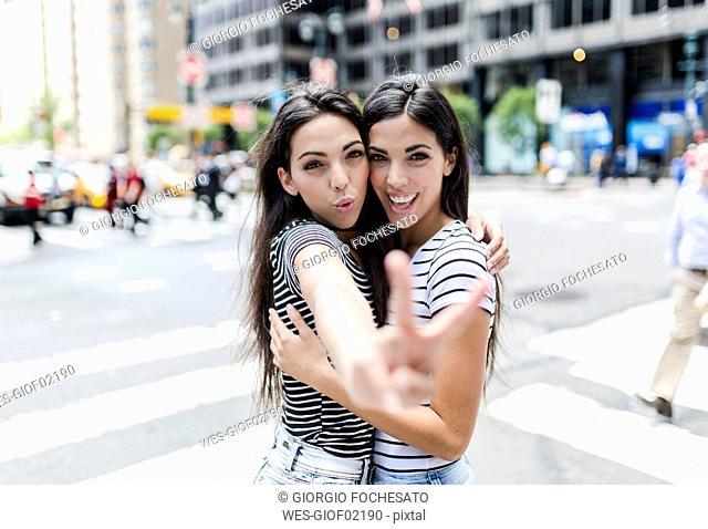 USA, New York City, portrait of two beautiful twin sisters in Manhattan having fun