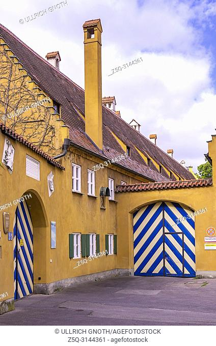 Fuggerei, Augsburg, Bavaria, Germany - Exterior view of the building complex with entrance gates at Jakob's Square (Jakobsplatz)
