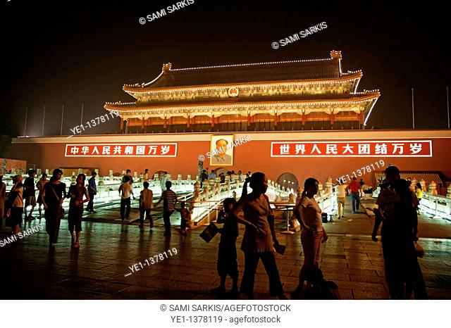 People passing by a portrait of Mao Zedong on the Temple of Heavenly Peace at night, Tiananmen Square, Beijing, China