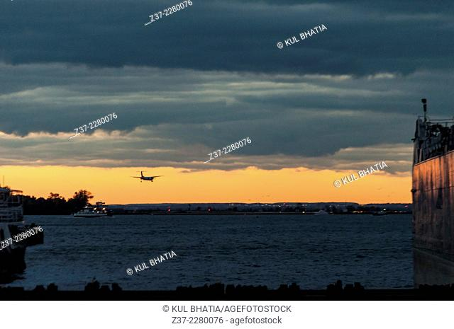 A small plane comes in for landing at sunset, Toronto, Ontario, Canada