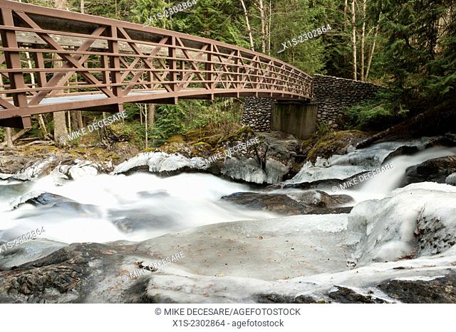 A footbridge directly over Deception Falls in Western Washington provides a safe passage and a spectacular view
