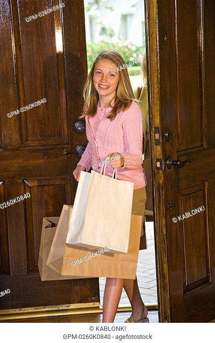 Portrait of girl holding shopping bags coming home