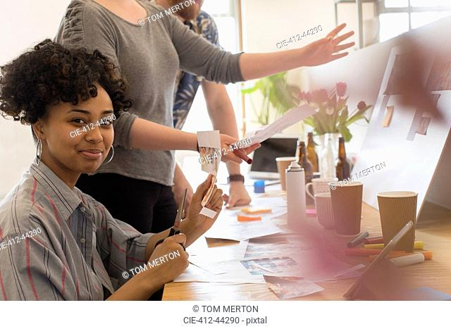 Portrait confident creative designer cutting photographs in office