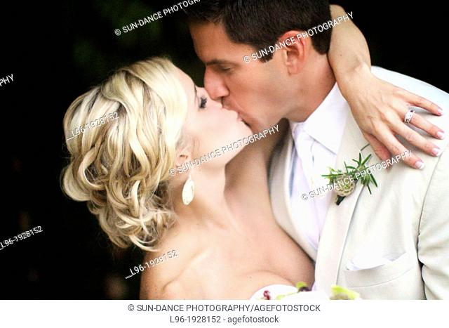 passionate kiss of a new bride and groom @ their garden wedding