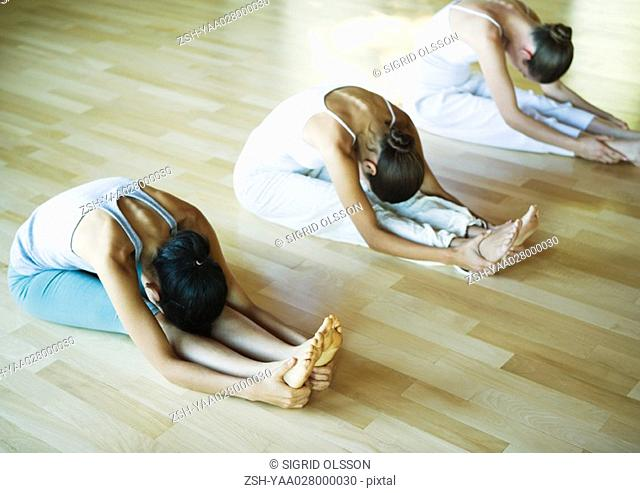 Yoga class, women doing seated forward bend