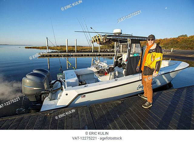 Fisherman standing on a dock beside his boat; Montauk, New York, United States of America