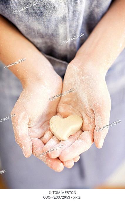 Close up of girl holding heart-shape dough