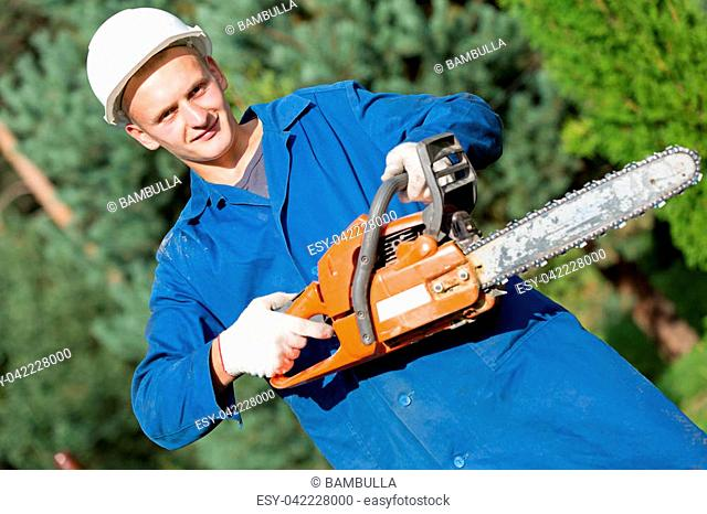 Smiling lumberjack Worker with Chainsaw in Work Wear on Forest background