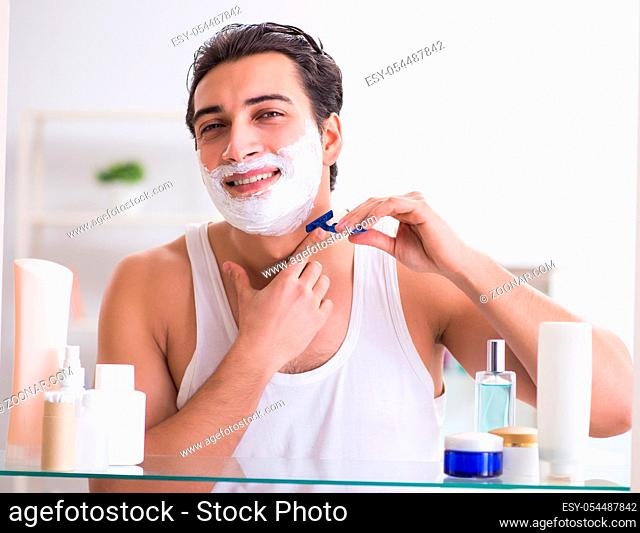 The young handsome man shaving early in the morning at home