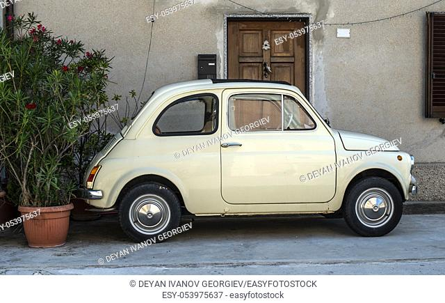 Small vintage italian car. Beige color old car in front of old house facade and flowers.