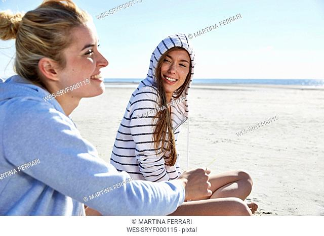 Two female friends wearing hoodies sitting on the beach