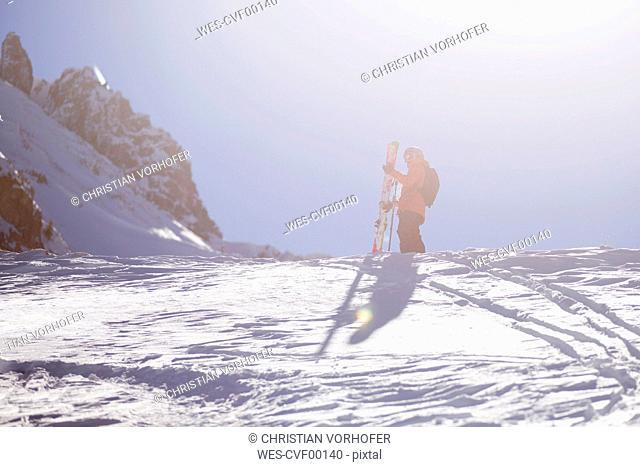Austria, Tyrol, Mutters, freeride skier ascending mountain