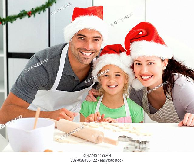 Happy family preparing Christmas cookies in the kitchen