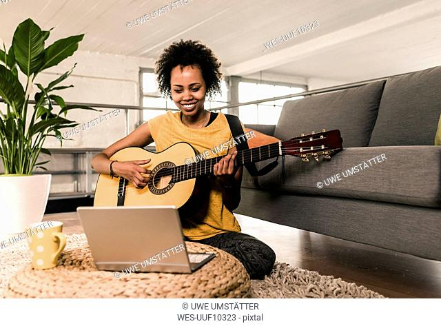 Smiling young woman at home playing guitar looking at laptop
