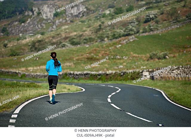 Rear view of female runner running on winding road, Capel Curig, Snowdonia, North Wales, UK