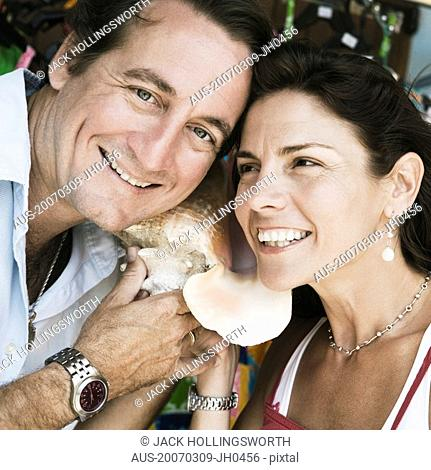Close-up of a mid adult couple listening to a conch shell and smiling