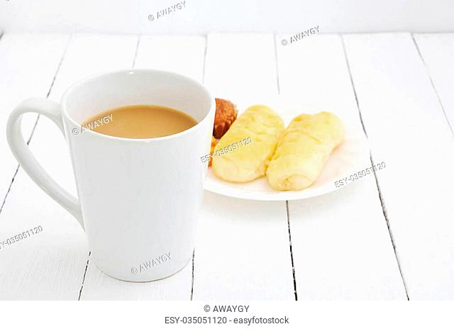 white coffee cup and bread snacks
