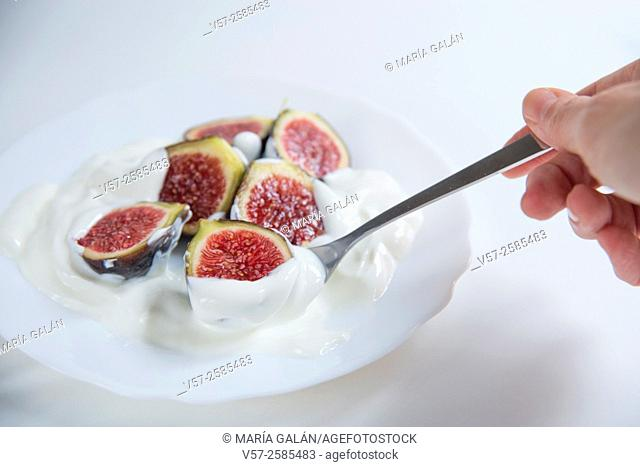 Hand having black figs with cream. Close view