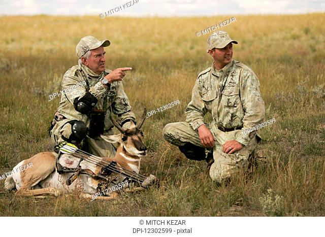 Mature Hunter And Younger Hunter With Dead Antelope On Prairie