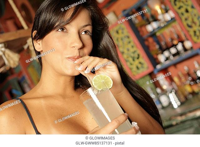 Close-up of a young woman drinking a glass of lemonade