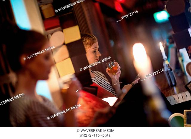 Beautiful woman using mobile phone while having wine