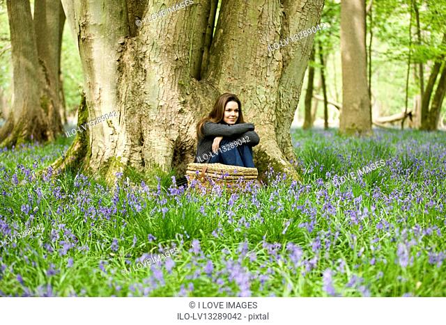 A young woman sitting under a tree, relaxing