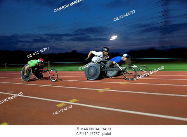 Paraplegic athletes speeding along sports track in wheelchair race at night
