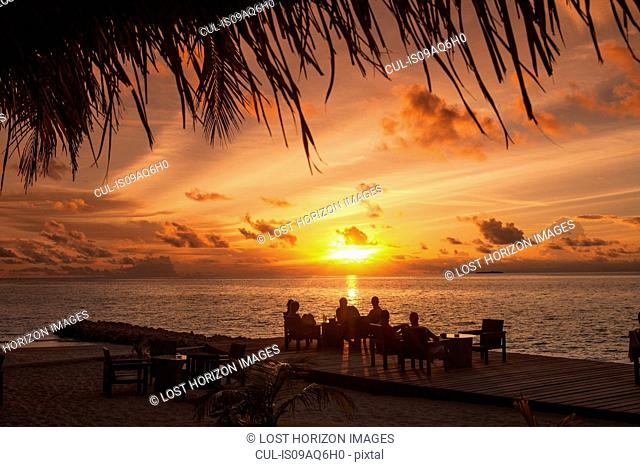 Silhouettes of people under palm trees at sunset, Ari Atoll, Maldives