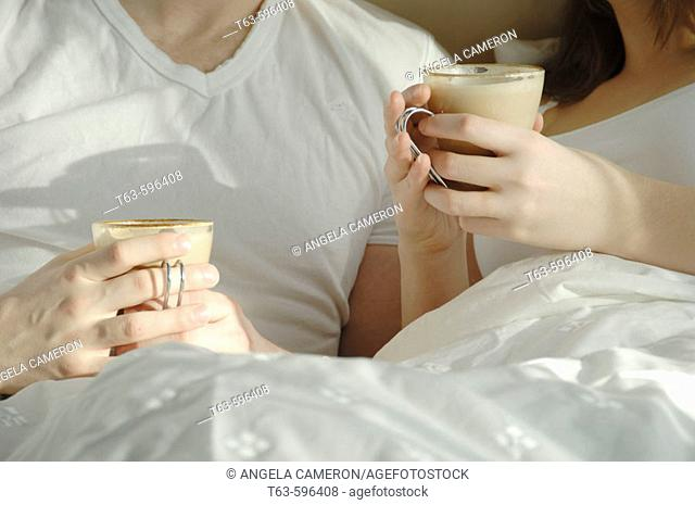 Young couple in bed drinking coffee together