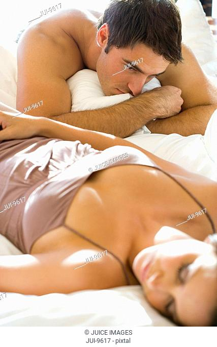 Young man looking at young woman lying on bed asleep