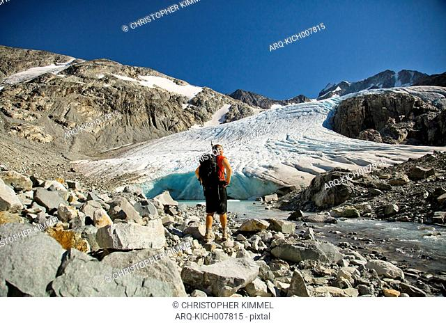 A Backpacker Standing At The Base Of The Wedgemount Glacier
