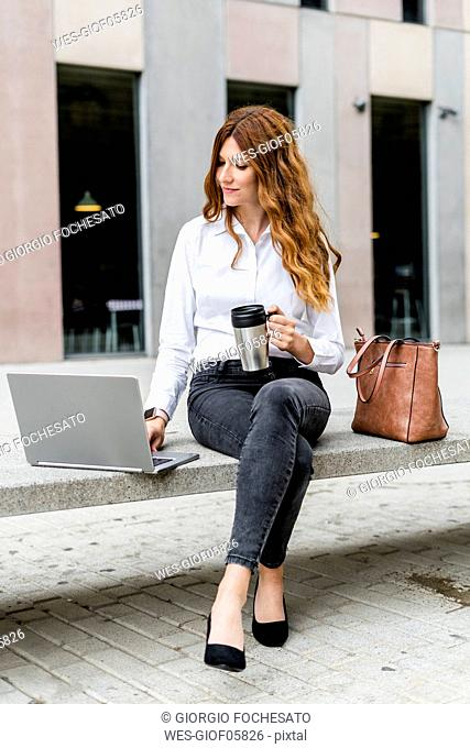 Young businesswoman sitting on bench in the city, working with laptop, drinking coffee