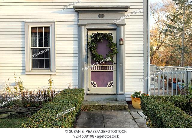 The front door of an old house decorated with a holiday wreath, in the town of Sandwich, Cape Cod, Massachusetts, United States