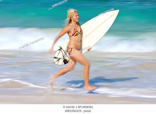 A young women runs along the ocean edge with surf board