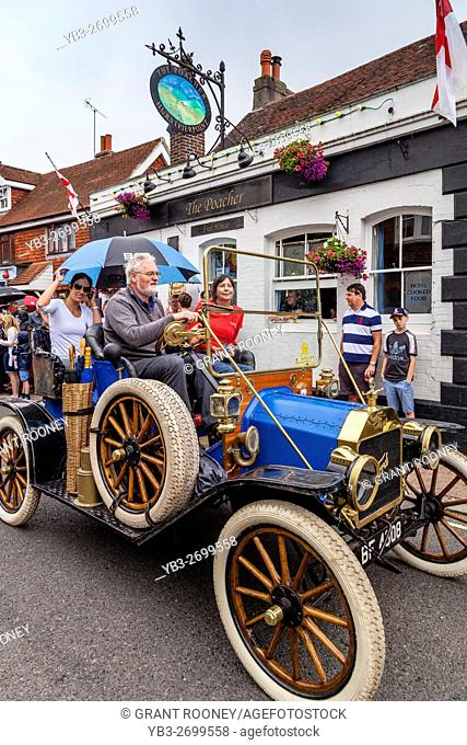 An Old Fashioned Car Takes Part In A Street Procession During The St Lawrence Fair, Hurstpierpoint, Sussex, UK