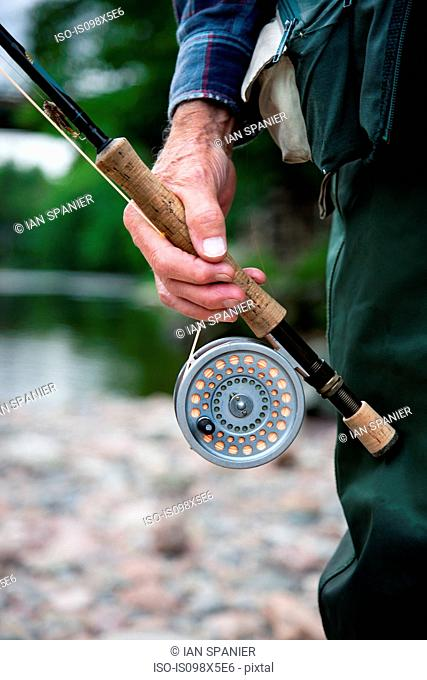 Man with fly fishing rod and reel, close up